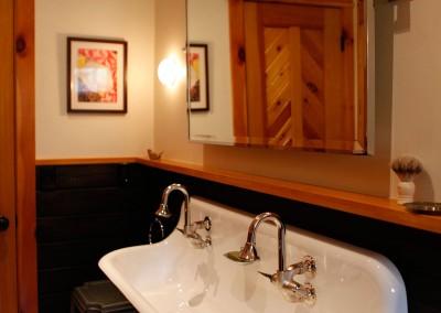 Twin farm style sink in warm wood trimmed bathroom.