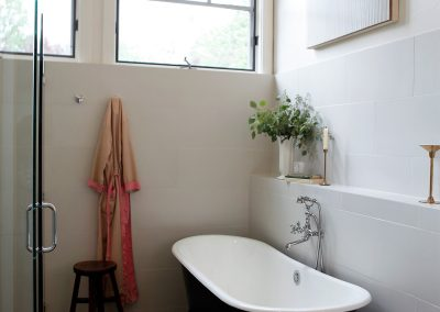 Clean white bathoom with hgh windows and black and white clawfoot tub.