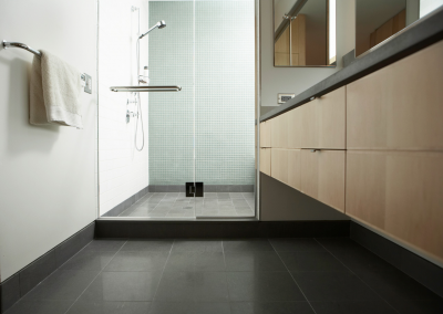 Crisp clean shower with clear glass doors and blakc tile floors.